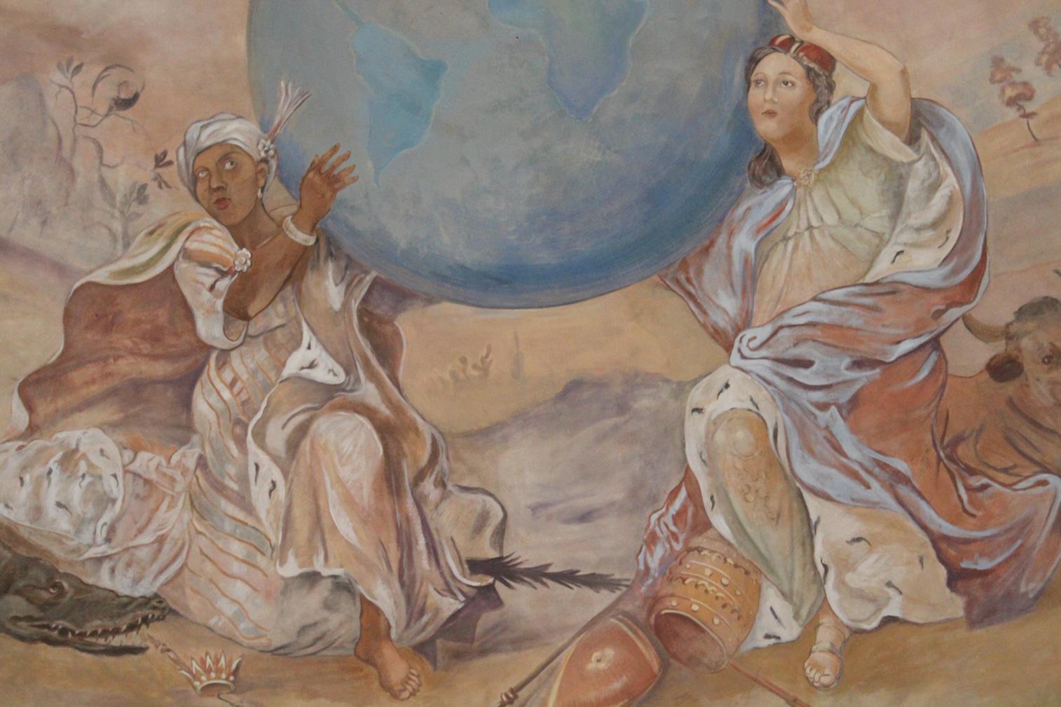 dwie kobiety trzymają kulę ziemską na której stoi Ignacy Loyola