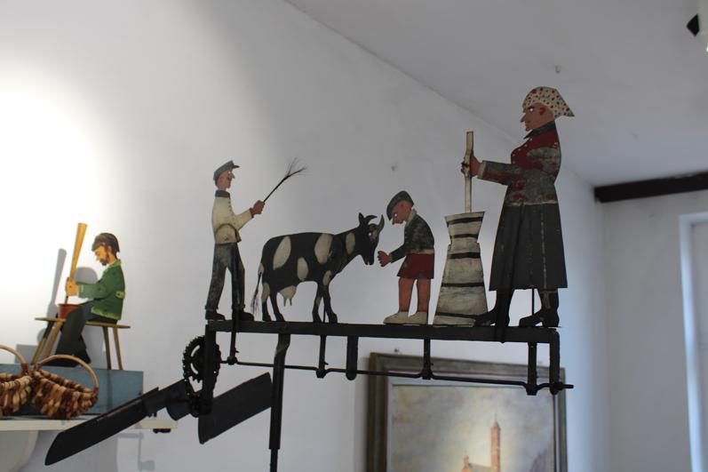 zabawka mechaniczna przedstawia rodzinę, która pasie krowę i matkę z maselnicą