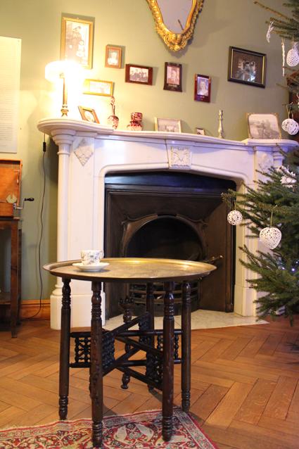 stolik kawowy, w tle kominek, na ścianie zdjęcia